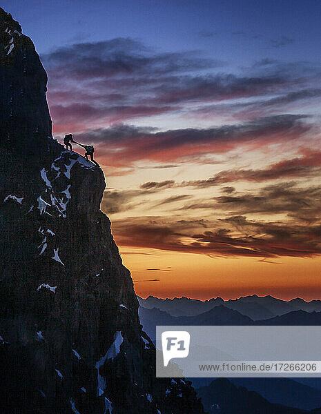 Frankreich  Haute Savoie  Chamonix  Silhouetten von Bergsteigern am felsigen Rand des Mont Blanc bei Sonnenuntergang