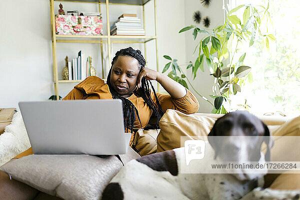 Frau liegt auf dem Sofa mit Hund und arbeitet am Laptop