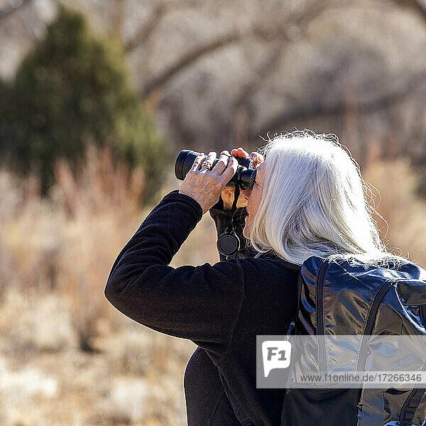 USA  Utah  Escalante  Seniorin benutzt Fernglas beim Wandern