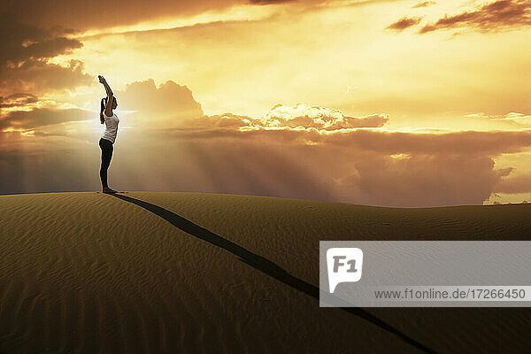 Dubai  Vereinigte Arabische Emirate  Frau übt Yoga auf Sanddüne in Wüste bei Sonnenuntergang