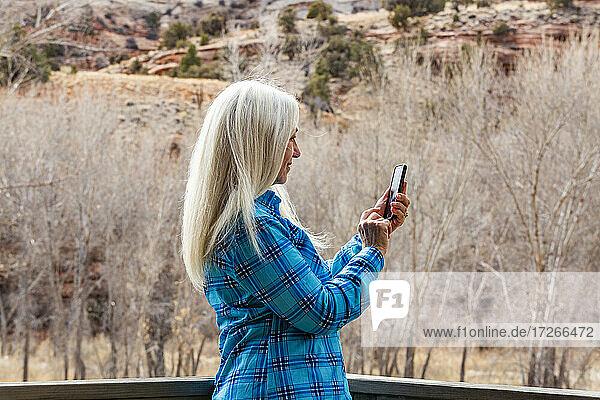 USA  Utah  Escalante  Frau mit Smartphone in Grand Staircase-Escalante National Monument