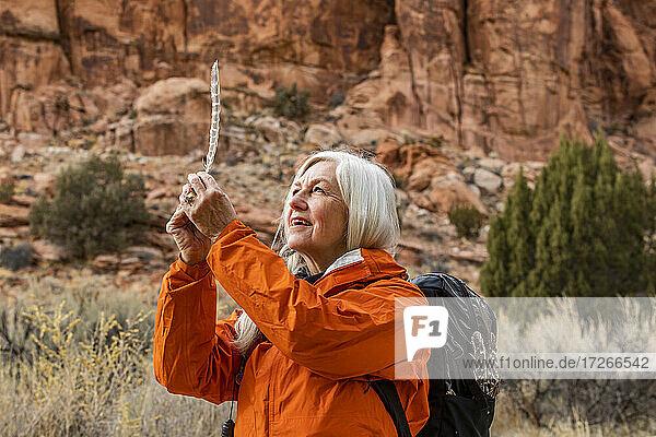 USA  Utah  Escalante  Frau schaut auf Feder beim Wandern im Grand Staircase-Escalante National Monument