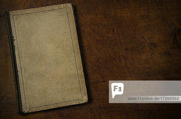Altes Buch mit leerem Einband  das auf einer alten hölzernen Schreibtischplatte liegt