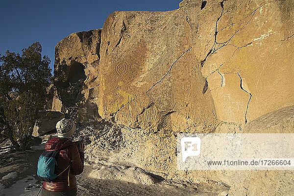 USA  New Mexico  Los Alamos  Tsankwai  Wanderin fotografiert Petroglyphen im Bandelier National Monument