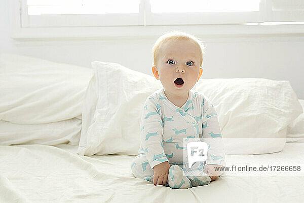Baby Junge mit offenem Mund sitzt auf dem Bett
