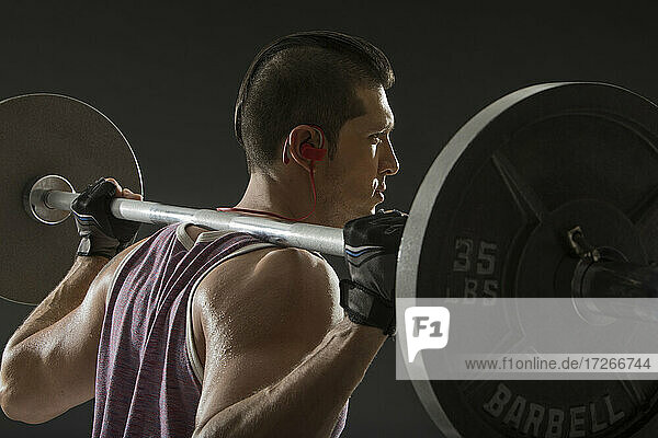 Muskulöser Mann beim Training mit Langhantel