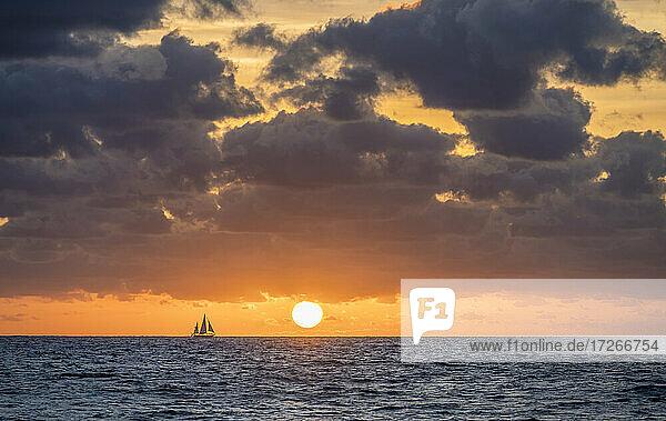 USA  Florida  Boca Raton  Sonnenaufgang über dem Meer mit Silhouette des Segelbootes in der Ferne