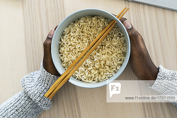 Hands of female holding noodle bowl at home