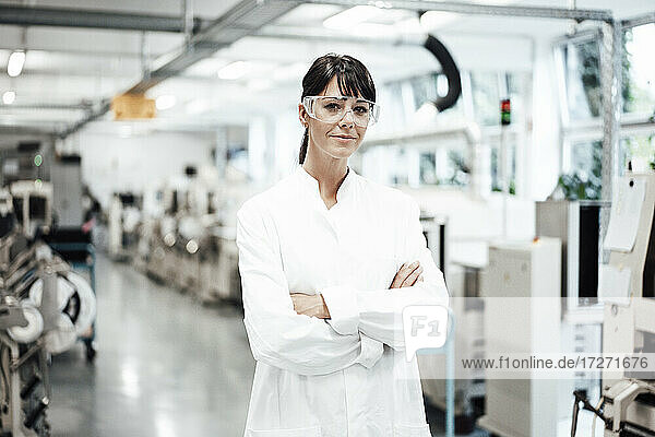 Confident female scientist standing with arms crossed in bright laboratory