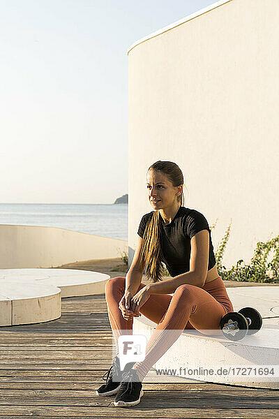 Sportswoman sitting on pedestal during sunrise