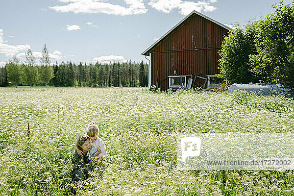 Mother and daughter amidst plants during sunny day