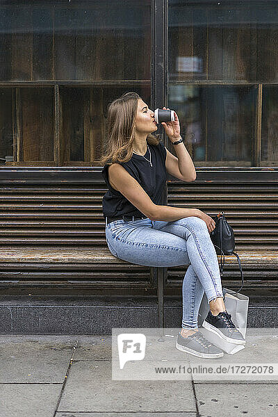Young woman drinking coffee while sitting on bench