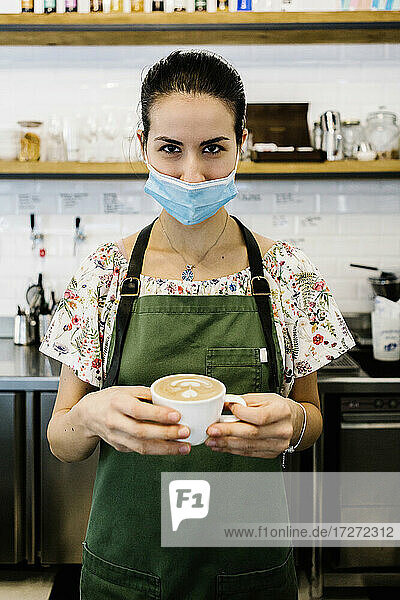 Young woman wearing face mask and apron with coffee cup standing at coffee shop