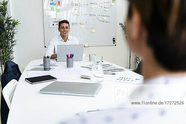 Lächelnder junger Mann im Gespräch mit einer Kollegin während einer Besprechung im Kreativbüro