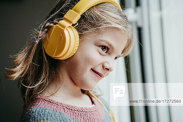 Smiling girl wearing headphones looking through window while standing at home