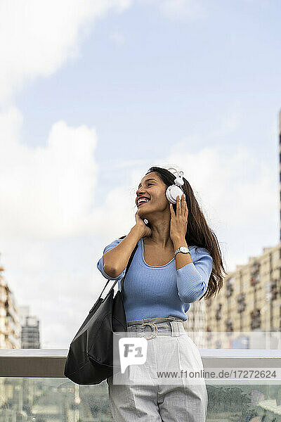 Glückliche Geschäftsfrau  die Musik über Kopfhörer hört  während sie sich an das Geländer gegen den Himmel lehnt