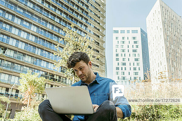 Handsome businessman using laptop while sitting against modern buildings
