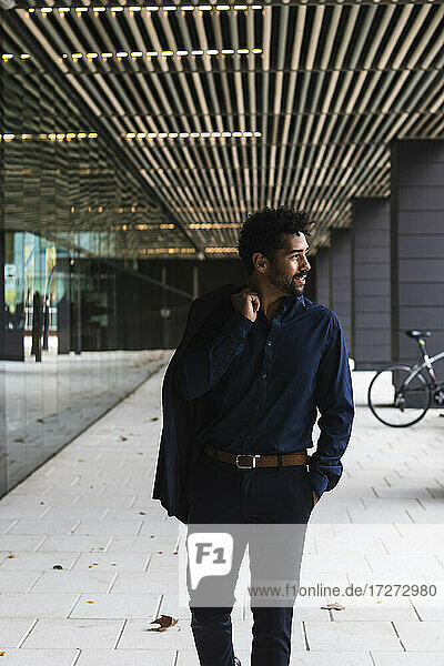 Smiling businessman holding blazer while walking in city