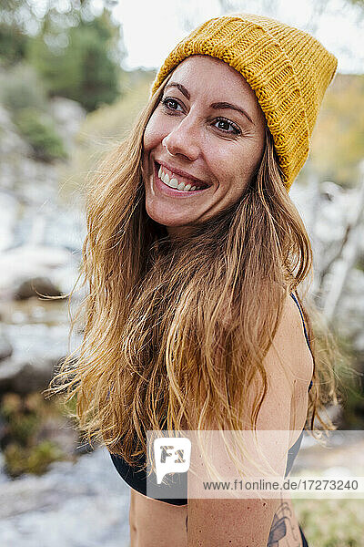 Smiling woman wearing knit hat looking away while standing in forest at La Pedriza  Madrid  Spain