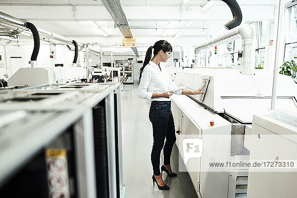 Businesswoman examining machinery while holding digital tablet in industry