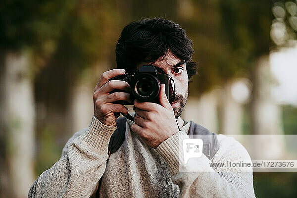 Mid adult man taking photo with camera while standing at forest