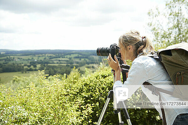 Active senior woman taking picture with camera of nature on sunny day