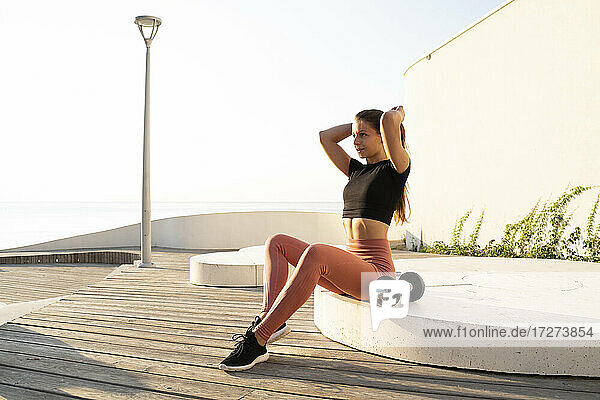 Female athlete with hand in hair sitting on pedestal during sunrise