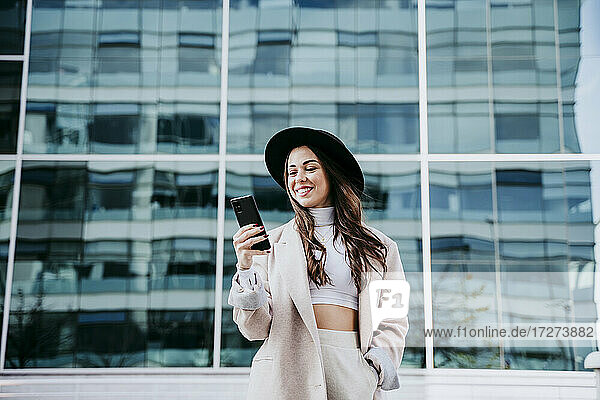 Smiling woman using smart phone while standing against building in city