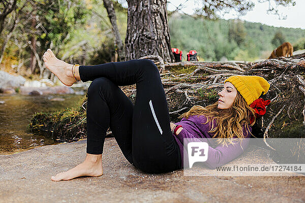 Woman wearing knit hat lying down by river in forest at La Pedriza  Madrid  Spain