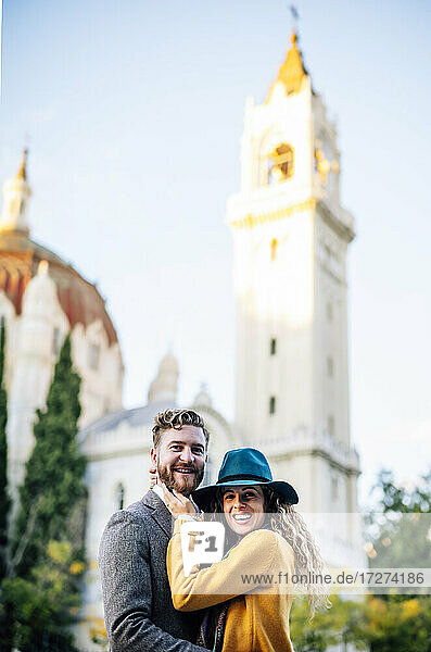 Smiling couple standing together against church
