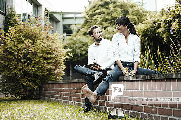 Carefree businesswoman discussing with male colleague while sitting on retaining wall