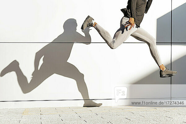 Young man running against white wall