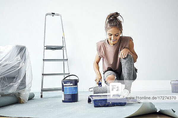 Smiling woman holding paint roller while crouching at home