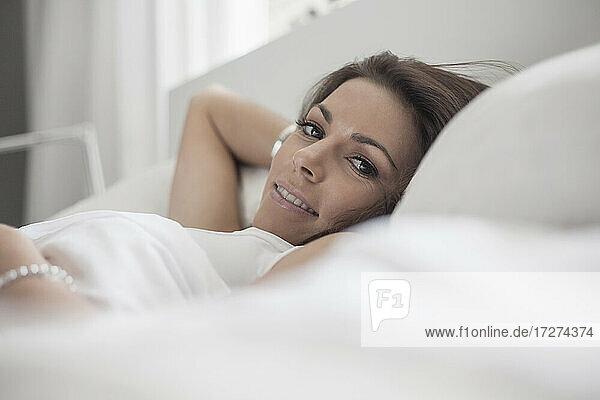 Frau ruht sich auf dem Bett im Schlafzimmer zu Hause aus
