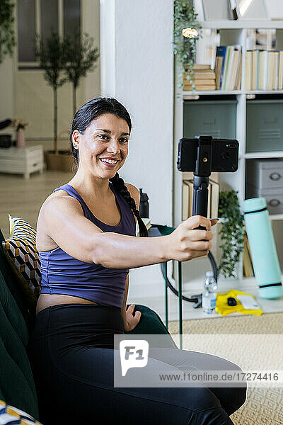 Female athlete video recording on camera while sitting at home
