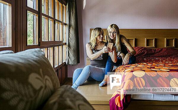 Lächelnde Frau  die ihr Smartphone mit ihrer Tochter im Teenageralter teilt  während sie im Schlafzimmer zu Hause sitzt