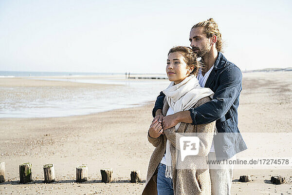 Young couple looking away while embracing at beach
