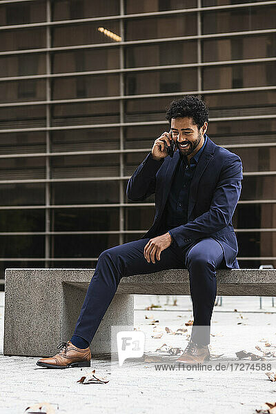 Businessman talking on smart phone while sitting on concrete in city