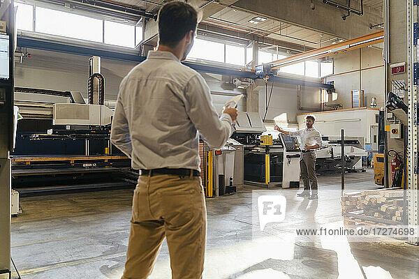 Businessman pointing toward equipment while talking with colleague at factory