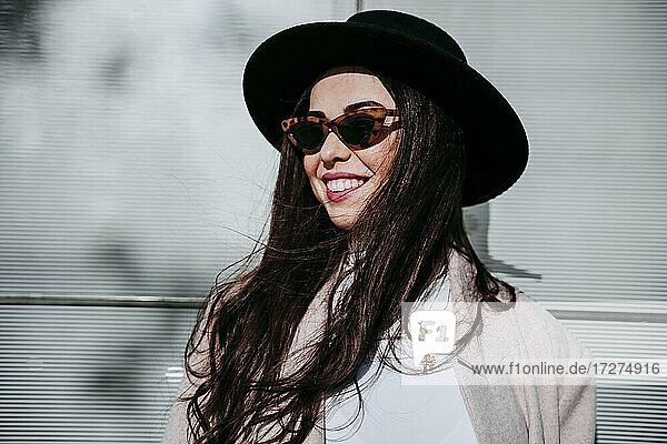 Beautiful smiling woman wearing hat while standing against wall