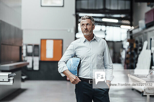 Thoughtful male engineer holding hardhat while standing in factory