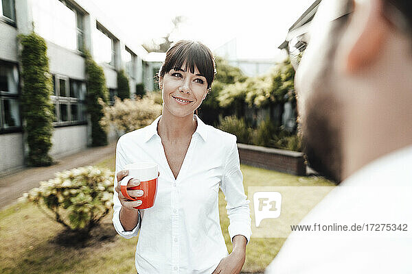 Smiling businesswoman with bangs holding coffee cup while looking at male colleague during discussion in break