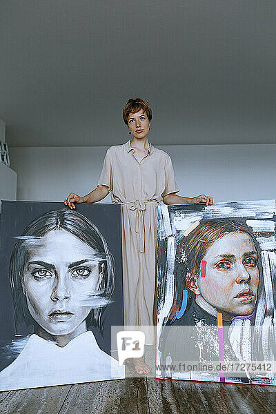 Mid adult female artist standing with paintings against wall in art studio