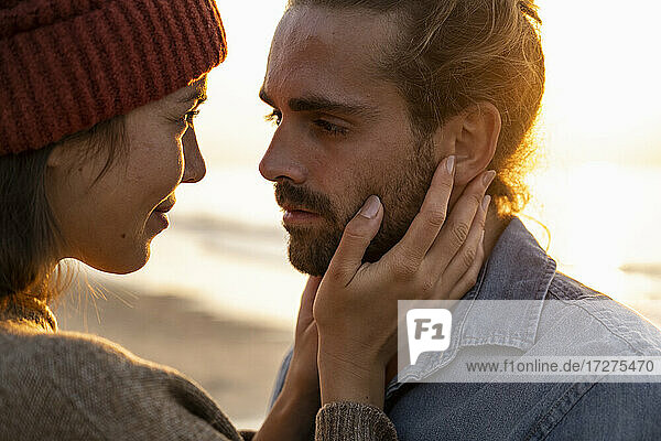 Romantic young couple standing face to face during sunset