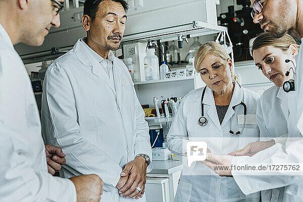 Mann und Frau benutzen ein digitales Tablet  während sie im Labor stehen