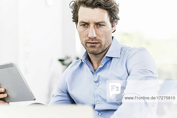 Man concentrating while using digital tablet sitting in office