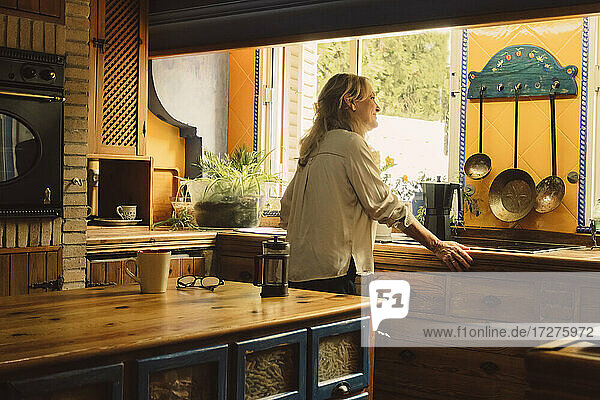 Senior woman looking through window while standing by coffee maker in kitchen at home