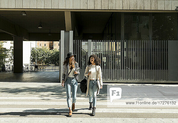 Female colleagues looking away while crossing street in city on sunny day