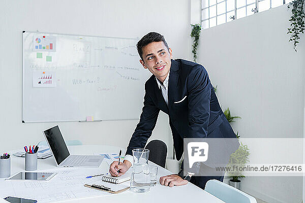 Thoughtful young handsome businessman looking away while writing in diary at office desk