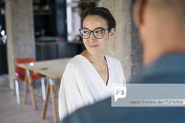 Businesswoman looking away while standing with man at office